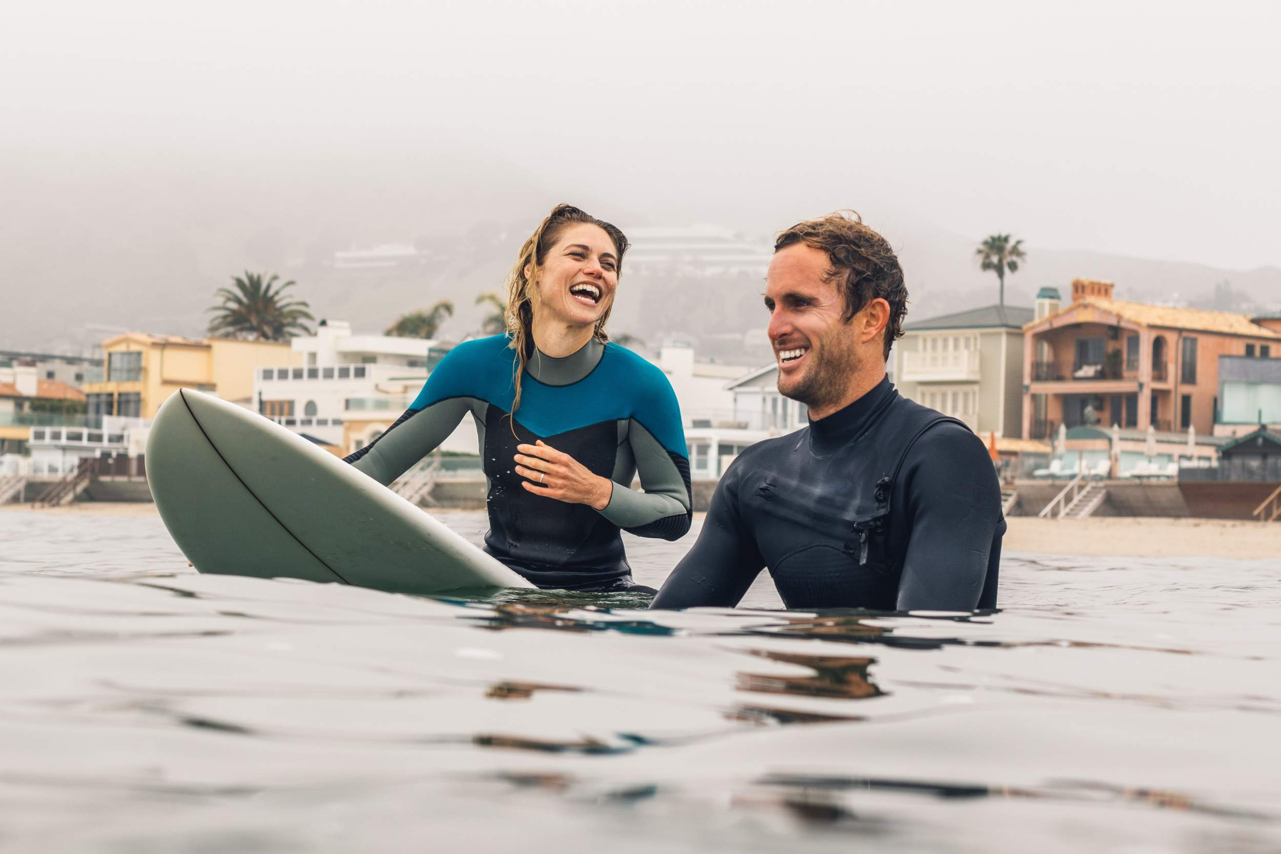 Two surfers in wet suits laugh in the water as they wait for the next big wave.