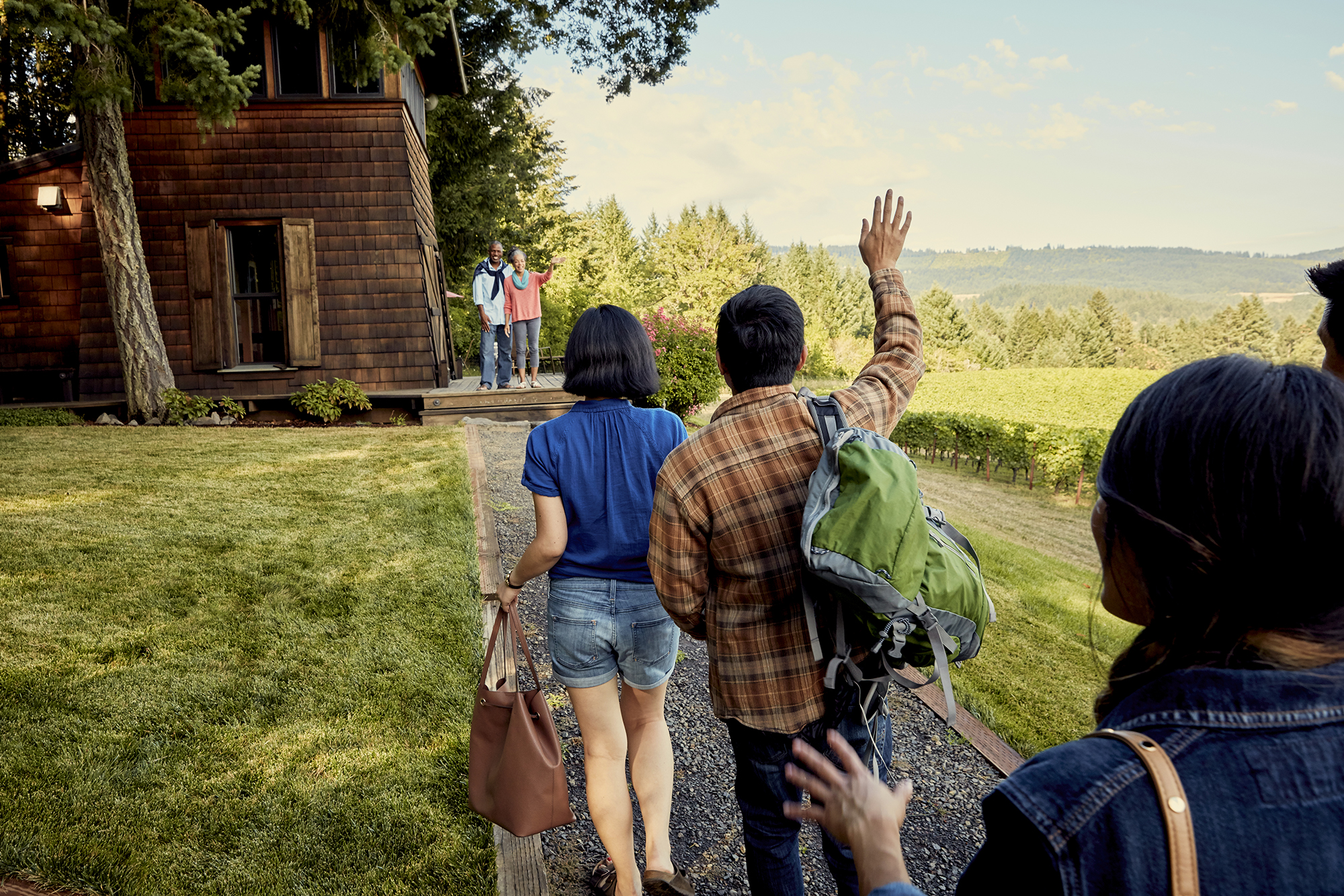 A group of friends are greeted by their hosts at their Airbnb listing.