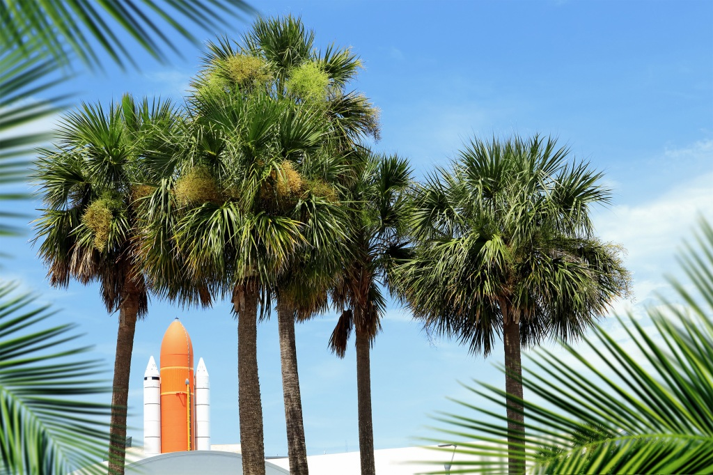 Kennedy space center entrance with space rocket and palm trees over blue sky in Cape Canaveral Florida, USA.
