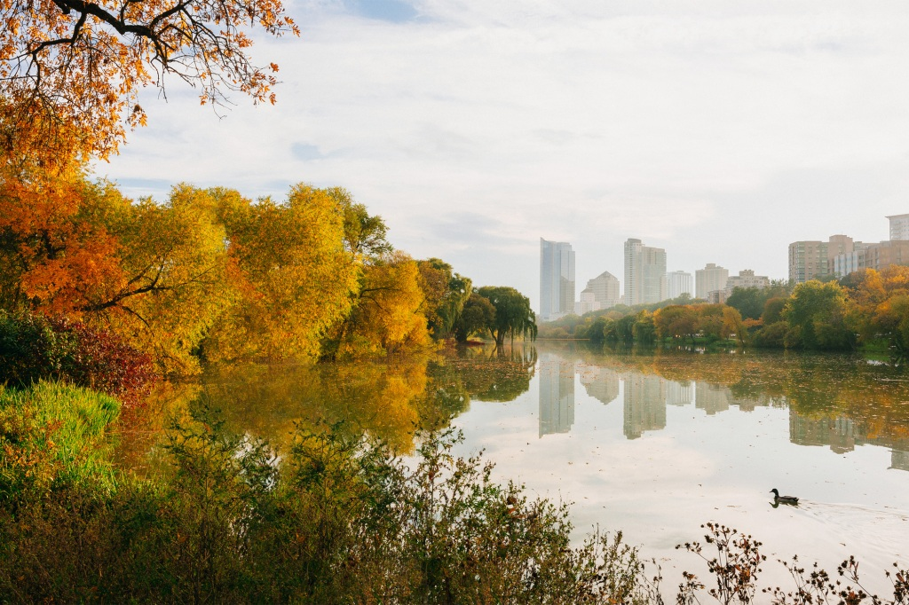 Scenic view of a lake by Milwaukee buildings against sky during autumn.