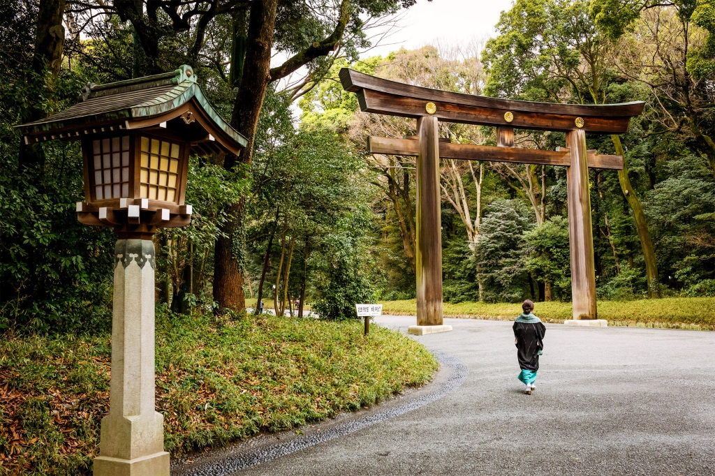A woman walks alone down a serene road in Tokyo, Japan.