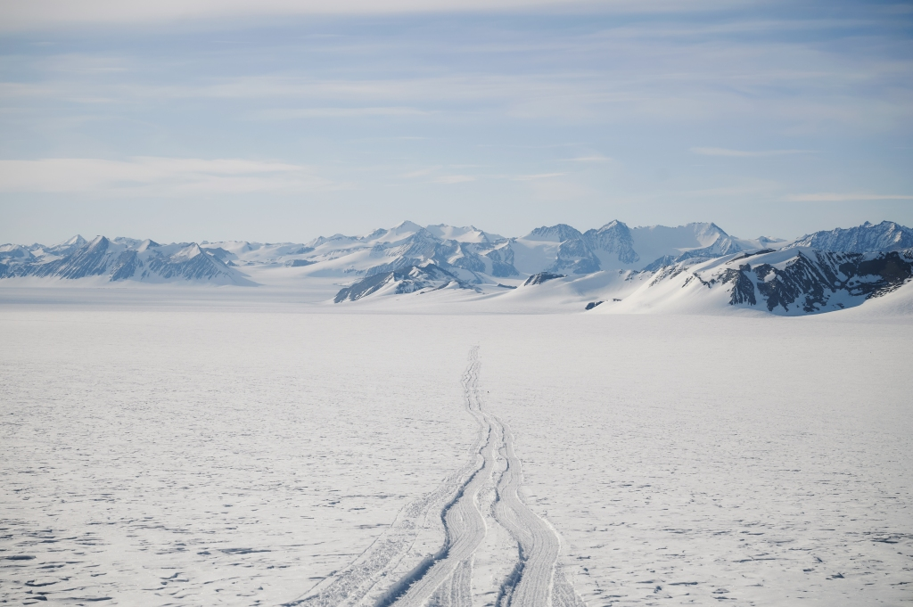 Tire tracks disappear into the distance on the awe-inspiring, frozen landscape of Antarctica