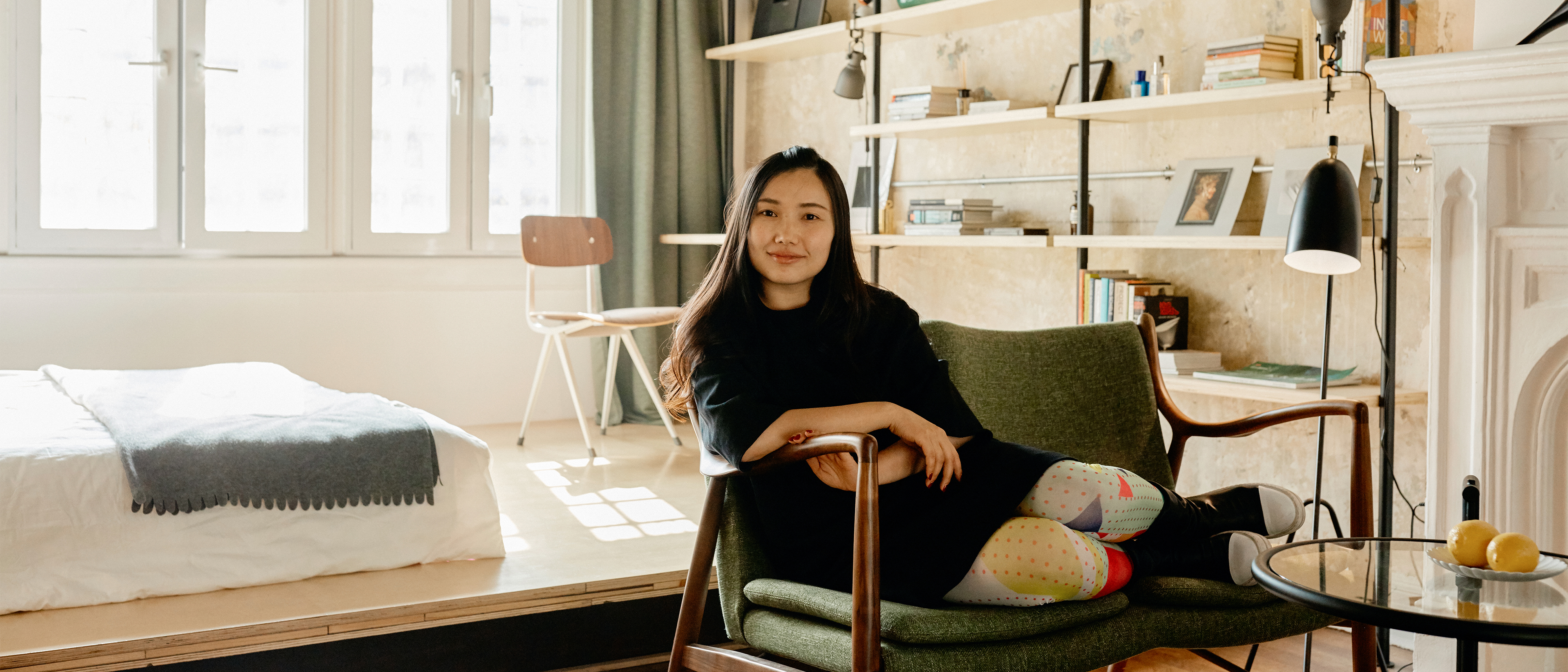 An Airbnb host in China sits on a green fabric chair in the bedroom of her listing.