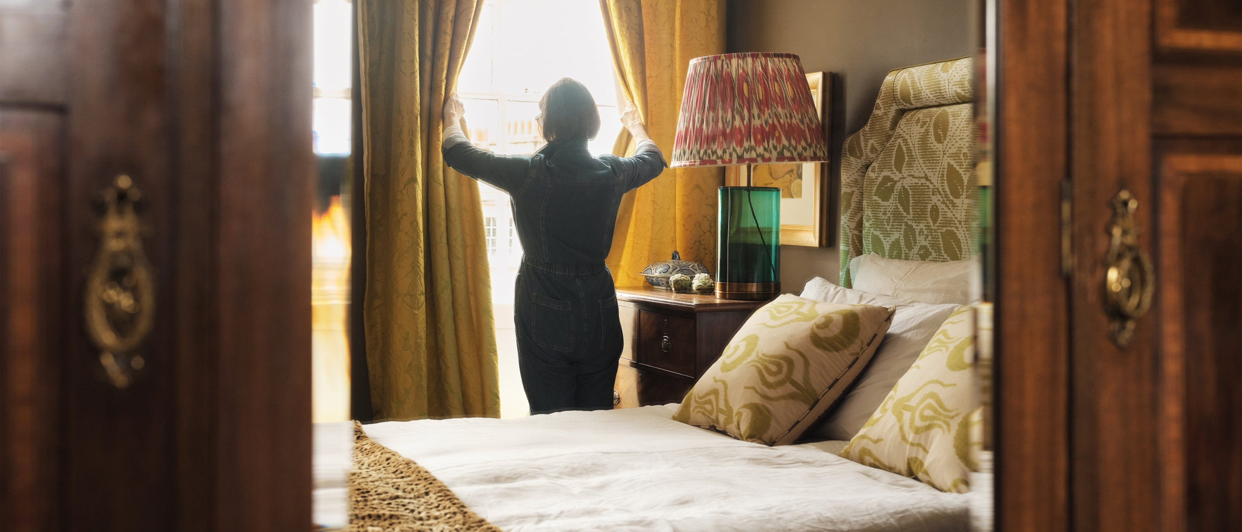 A woman opens the curtains and light pours into the bedroom of her Airbnb listing.