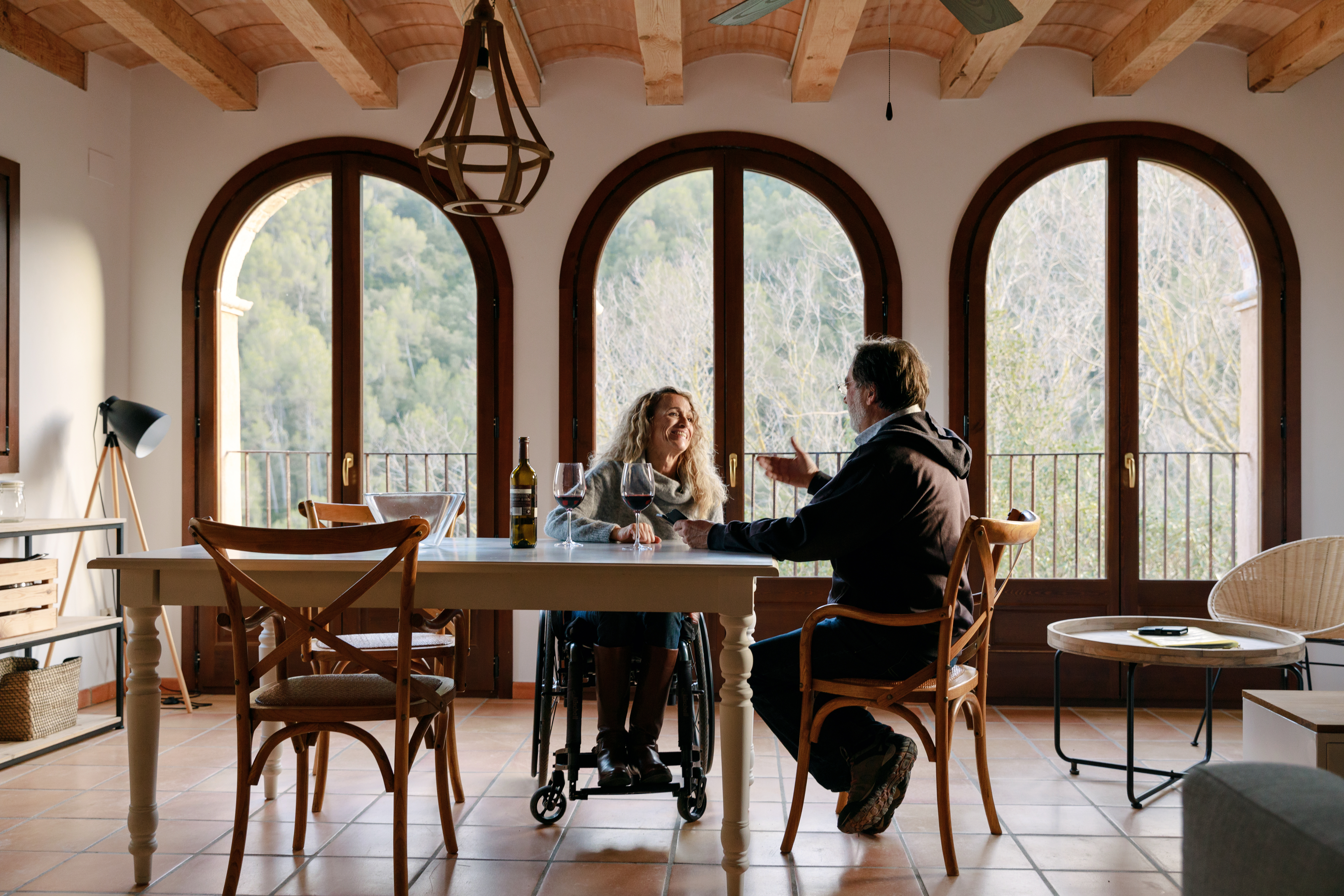 A pair, including a wheelchair user, sat at a kitchen table in Spain
