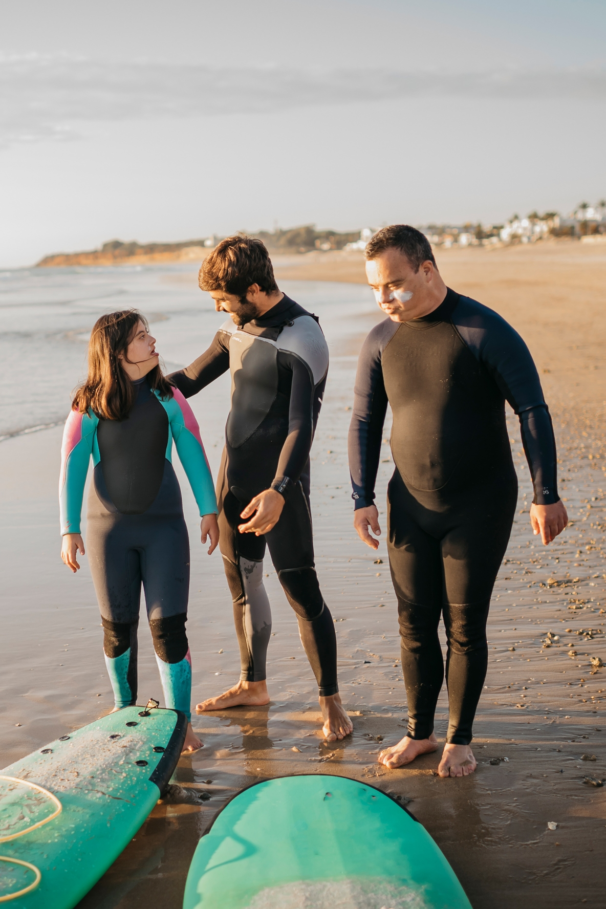 Three people participating in a Therapeutic Surfing lesson in La Barrosa, Spain