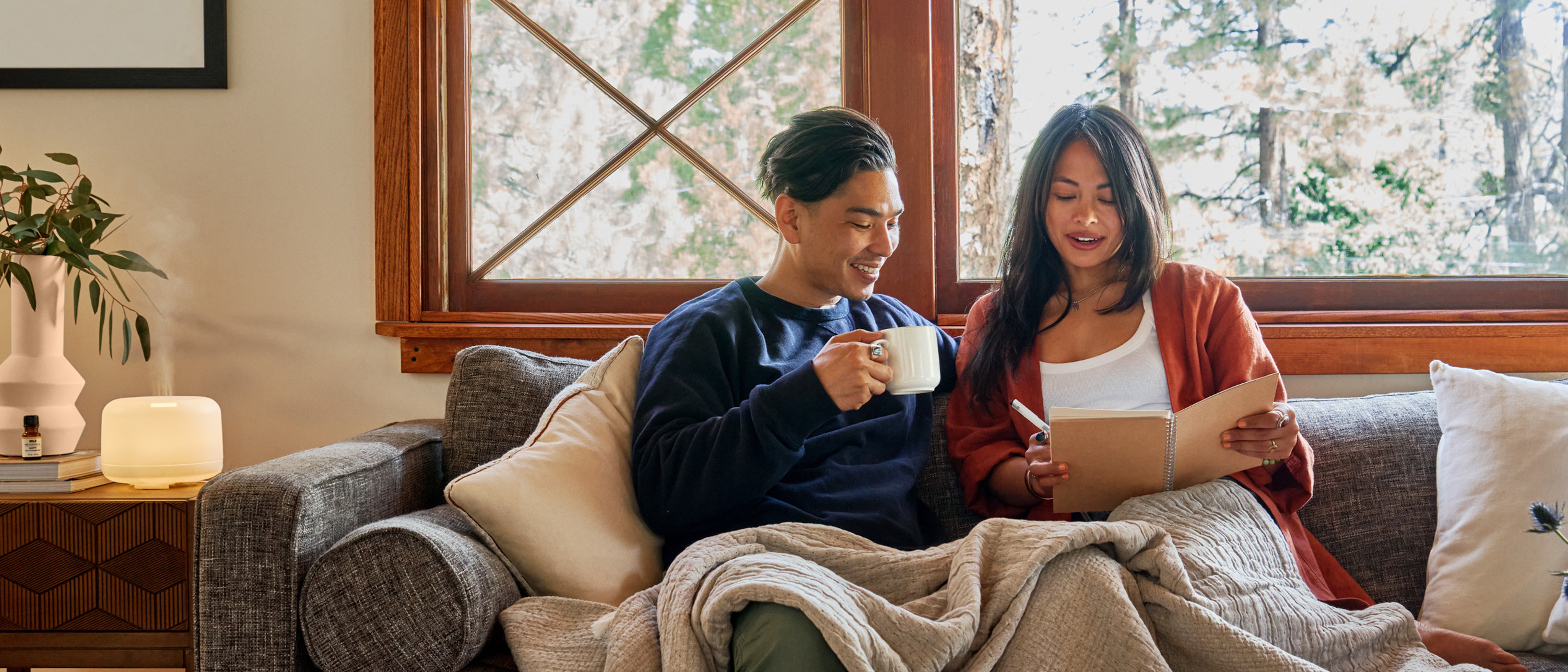 Couple sitting on the couch with a blanket and mugs, looking at a journal with an essential oil diffuser on the table next to them.