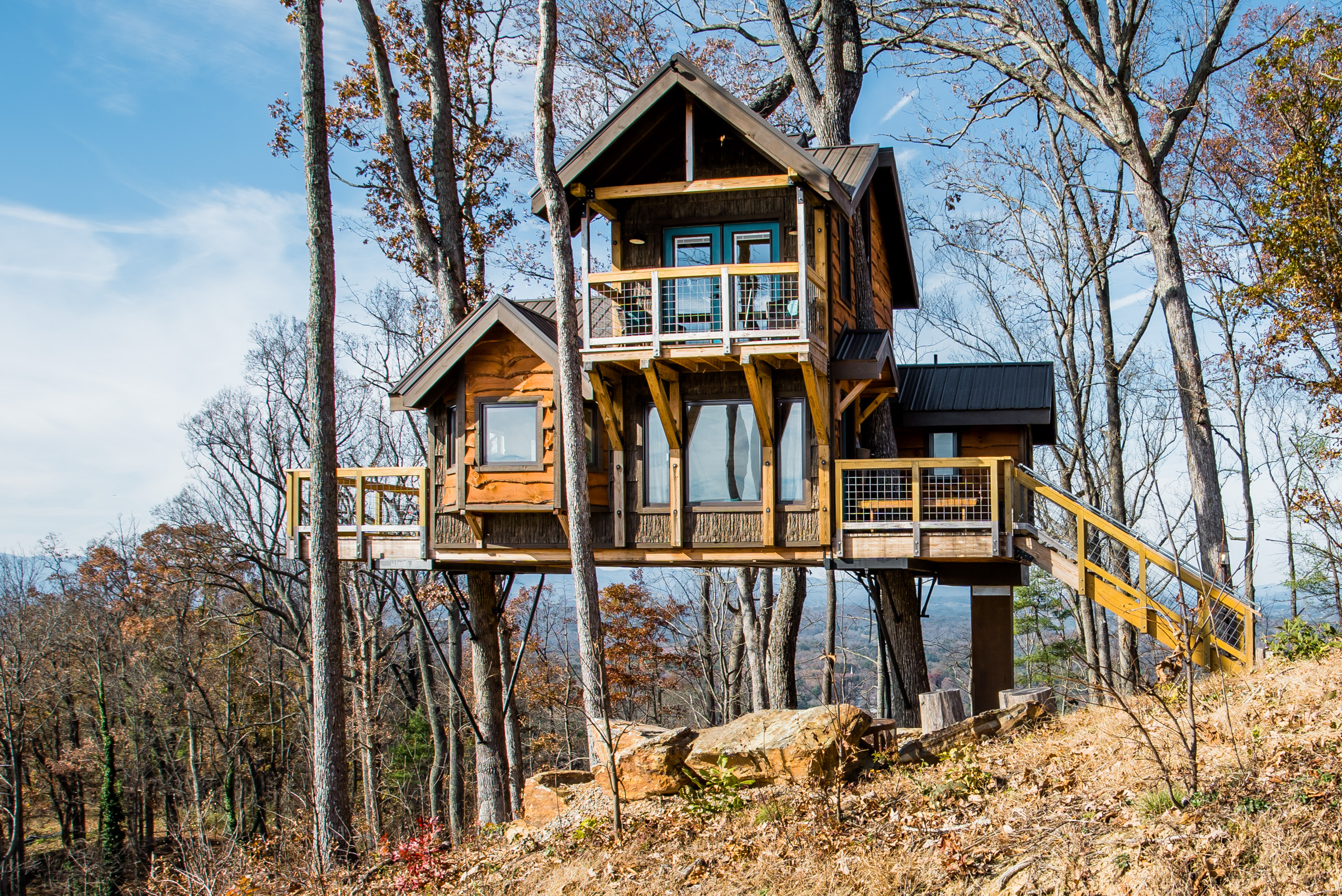 Modern treehouse with three wings elevated amongst bare trees on a hillside.